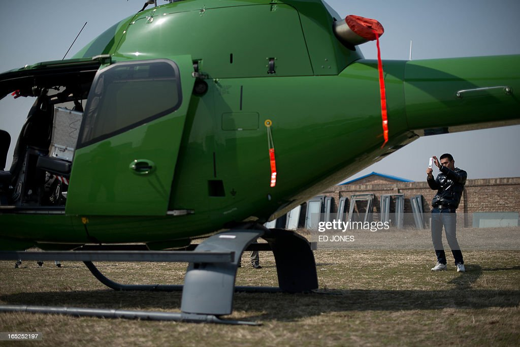 A man takes a photo of a Eurocopter EC120B helicopter prior to a demonstration flight for the media at an airfield adjacent to an 'aircraft supermarket' on the outskirts of Beijing on April 2, 2013. Selling gliders, helicopters, and powered light aircraft for prices up to 50 million yuan (around 8 million USD) the joint-venture trading company run by Beijing International United Flight Club is the first of its kind in the city and hopes to open the market to public buyers, although it has sold aircraft to club members for over 20 years. However, low-altitude airpace in China is still tighly controlled and despite hopes of liberalisation for private pilots, reports of secret or 'black' flights are not uncommon and are widely considered to be on the rise. AFP PHOTO / Ed Jones