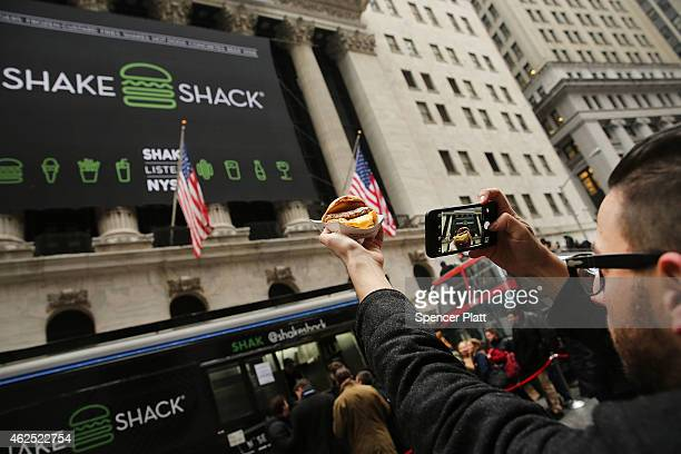 A man takes a photo of a free Shake Shack hamburger he got outside the New York Stock Exchange during the burger company's IPO on January 30 2015 in...