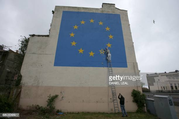TOPSHOT A man takes a photo of a recently painted mural by British graffiti artist Banksy depicting a workman chipping away at one of the stars on a...