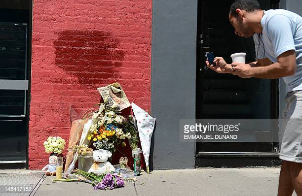 A man takes a photo of a street shrine to sixyearold Etan Patz who disappeared 33 years ago set in front of the building where suspect Pedro...