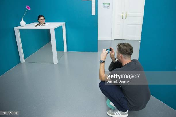 A man takes a photo of a woman inside of the Head on the Plate Room an exhibition part of the Museum of Illusions in Vienna Austria on October 16...