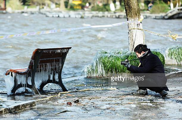 A man takes a photo of an icecovered bench at West Lake amid the cold in Hangzhou in eastern China's Zhejiang province on January 24 2016 Much of...