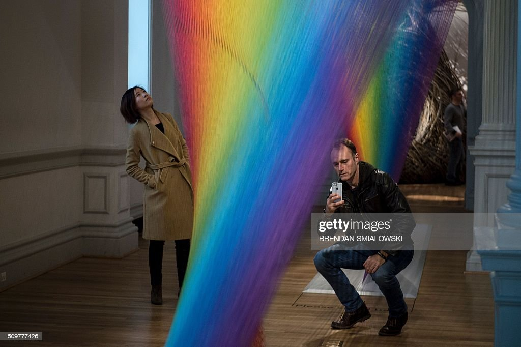 A man takes a photo of Gabriel Dawe's Plexus A1 exhibit at the Smithsonian's Renwick Gallery February 12, 2016 in Washington, DC. / AFP / Brendan Smialowski / RESTRICTED TO EDITORIAL USE - MANDATORY MENTION OF THE ARTIST UPON PUBLICATION - TO ILLUSTRATE THE EVENT AS SPECIFIED IN THE CAPTION