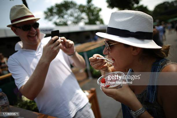 A man takes a photo of his friend eating strawberries and cream on day eleven of the Wimbledon Lawn Tennis Championships at the All England Lawn...
