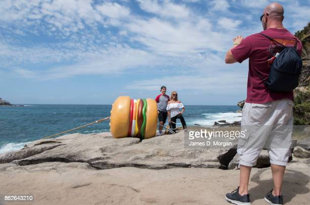 A man takes a photo of his wife and son beside 'What a Tasty Looking Burger' by James Dive at Sculpture By The Sea on October 18 2017 in Sydney...