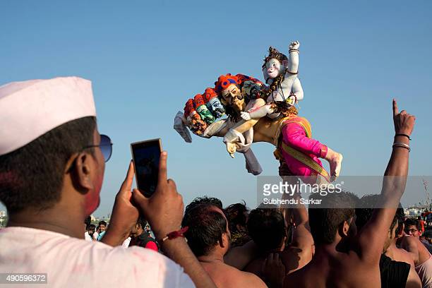 A man takes a photo of lord Ganesha while it is taken for immersion into the Arabian sea at Girgaum Chowpatty beach in Mumbai Ganesha Chaturthi or...
