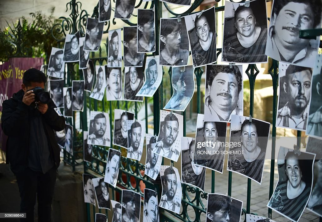 A man takes a photo of photos of killed journalists stuck on the fence of the Veracruz state representation office during a journalists protest in Mexico City on February 11, 2016. Mexican journalist Anabel Flores Salazar's funeral took place Wednesday after she was found killed at a road after being kidnapped Monday in Veracruz state, one of the most dangerous for journalists. AFP PHOTO/RONALDO SCHEMIDT / AFP / RONALDO SCHEMIDT