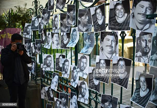 A man takes a photo of photos of killed journalists stuck on the fence of the Veracruz state representation office during a journalists protest in...