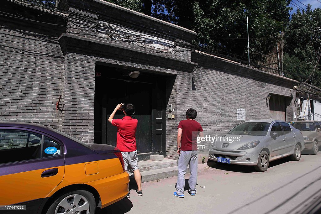 A man (L) takes a photo of the gate at one of the houses that belongs to fallen Chinese political star Bo Xilai and his family in Beijing on August 23, 2013. The trial of fallen Chinese politician Bo Xilai, which had been widely expected to last no more than two days, will continue into a third day on August 24, the court said. Bo, once one of China's highest-flying politicians, faces charges of bribery, embezzlement and abuse of power which emerged after the lurid scandal triggered by the death of British businessman Neil Heywood. CHINA