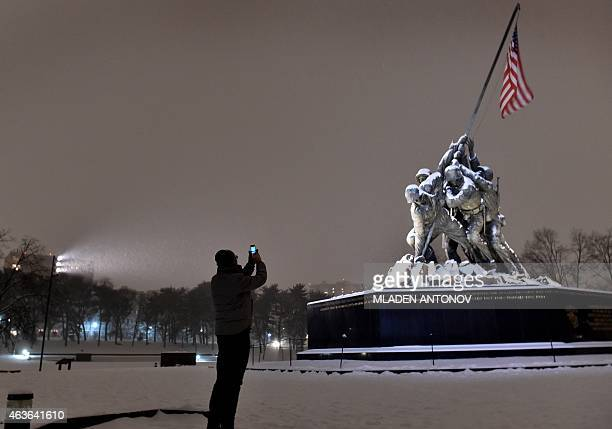 A man takes a photo of the snow covered Iwo Jima memorial in Washington DC on February 16 2015 The eastern United States braced for an arctic...