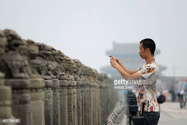 A man takes a photo on the Marco Polo bridge or Lugouqiao in west Beijing on July 7 on the the 77th anniversary of the Marco Polo Bridge incident a...