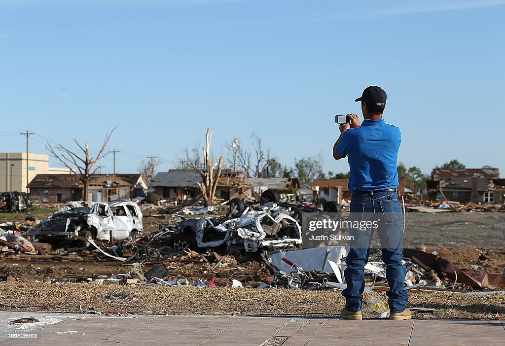A man takes a photo with his cell phone of a neighborhood damaged by a tornado June 2, 2013 in Moore, Oklahoma. Residents of Moore, Oklahoma continue to recover and sift through the remains of their homes two weeks after a devastating EF-5 tornado ripped through the town killing 24 people and destroying hundreds of homes and businesses.