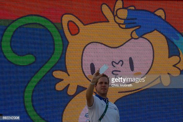 A man takes a photo with the Rio 2016 mascot 'Vinicius' in front of a screen at Olympic Park on Day 15 of the Rio 2016 Olympic Games on August 19...