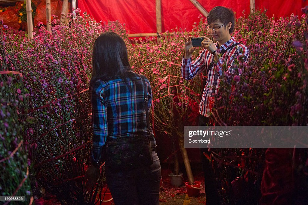 A man takes a photograph amongst peach blossoms displayed for sale for the Lunar New Year in the Mongkok district of Hong Kong, China, on Thursday, Feb. 7, 2013. Hong Kong's stock market will be shut for three days next week for the Lunar New Year holidays, while markets in mainland China will be closed for the whole week. Photographer: Lam Yik Fei/Bloomberg via Getty Images