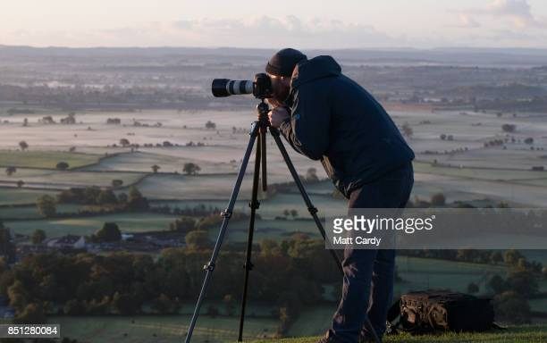 A man takes a photograph as the autumn sun rises over the Somerset Levels viewed from Glastonbury Tor near Glastonbury on September 22 2017 in...