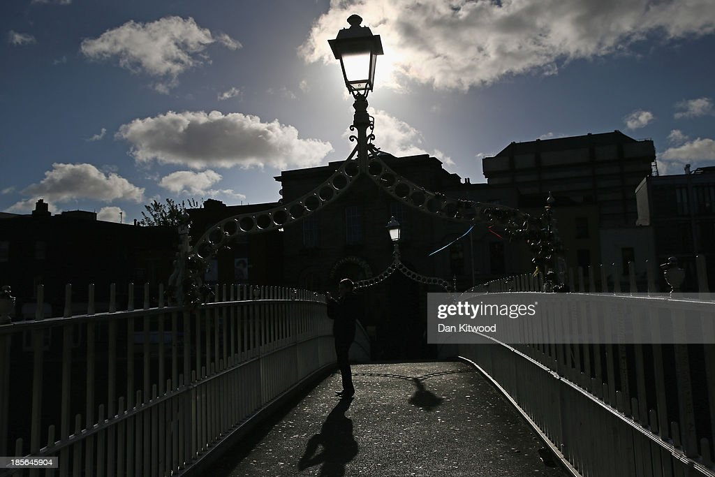 A man takes a photograph from a footbridge over the Liffey on October 23, 2013 in Dublin, Ireland. Dublin is the capital city of The Republic of Ireland situated in the province of Leinster at the mouth of the River Liffey. The greater Dublin area has a population of around 1.5 Million people.