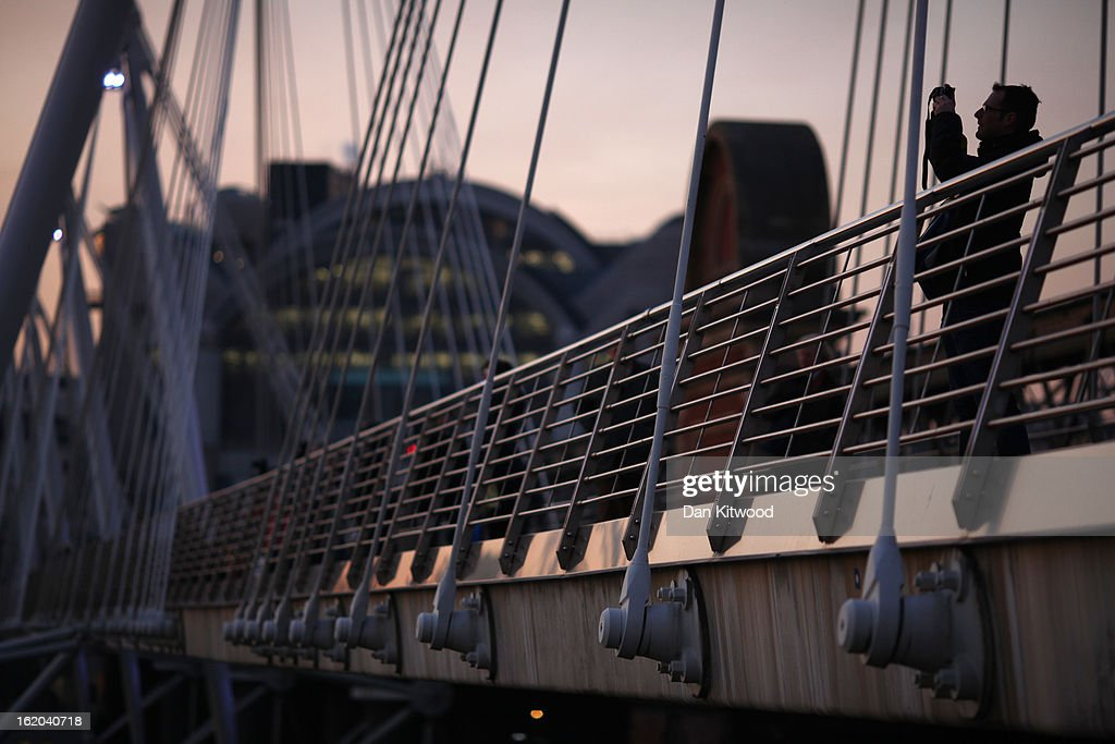 A man takes a photograph from Jubilee Bridge at sunset on London's Southbank on February 18, 2013 in London, England.