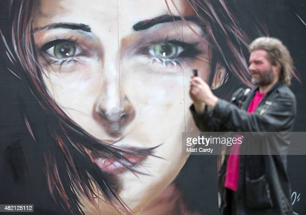 A man takes a photograph in front of a piece of street art as part of the ongoing Upfest 2015 festival being held in Bedminster on July 27 2015 in...