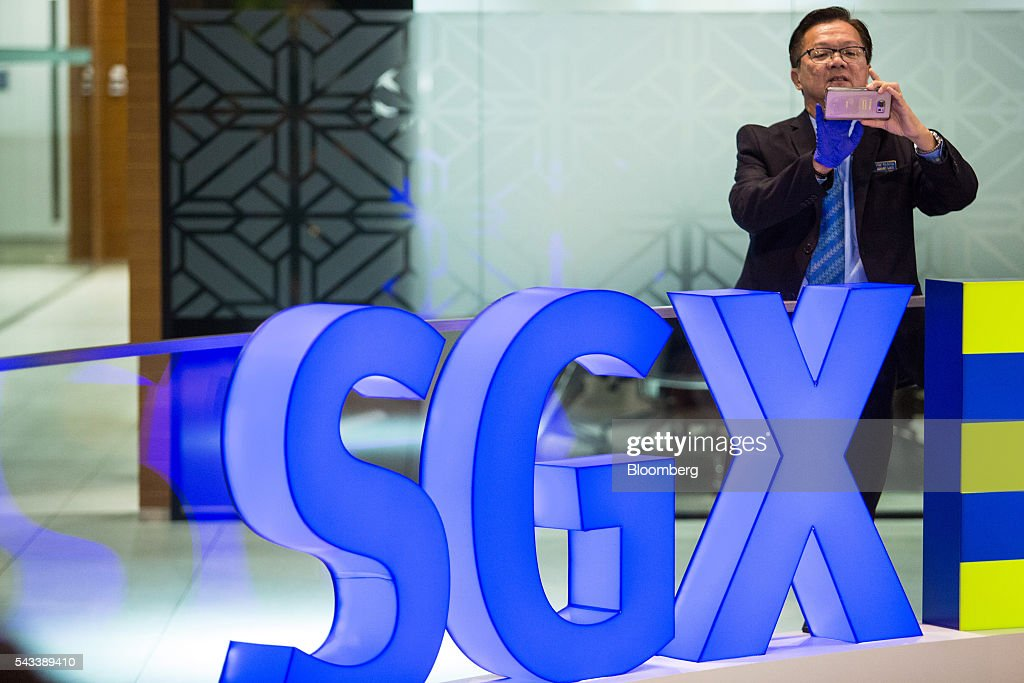 A man takes a photograph near Singapore Exchange Ltd. (SGX) signage displayed inside the SGX Centre, which houses the bourse's headquarters, in Singapore, on Tuesday, June 28, 2016. Days after the surprise U.K. vote for Brexit started roiling global markets, prospects for greater monetary and fiscal stimulus are becoming clear in Asia, even as the region's relative growth dynamism offers it resilience. Photographer: Nicky Loh/Bloomberg via Getty Images