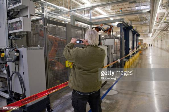 A man takes a photograph of a machine for auction at Solyndra Inc headquarters in Fremont California US on Monday Dec 12 2011 Solyndra Inc the...