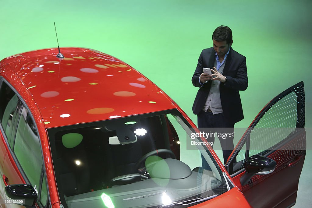 A man takes a photograph of a Renault Clio automobile, produced by Renault SA, on the first day of the 83rd Geneva International Motor Show in Geneva, Switzerland, on Tuesday, March 5, 2013. This year's show opens to the public on Mar. 7, and is set to feature more than 100 product premiers from the world's automobile manufacturers. Photographer: Chris Ratcliffe/Bloomberg via Getty Images