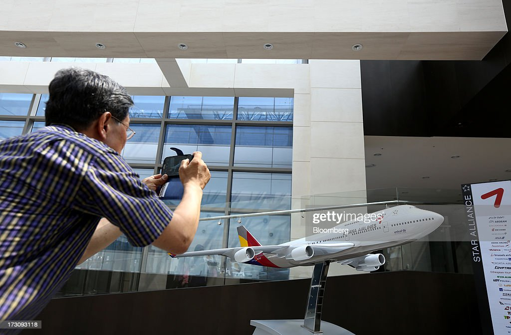 A man takes a photograph of an Asiana Airlines Inc. model aircraft displayed at the company's headquarters in Seoul, South Korea, on Sunday, July 7, 2013. A Boeing Co. 777 flown by South Korea's Asiana Airlines crashed while landing in San Francisco yesterday, killing two people as passengers escaped down emergency slides before a fire swept through the plane. Photographer: SeongJoon Cho/Bloomberg via Getty Images