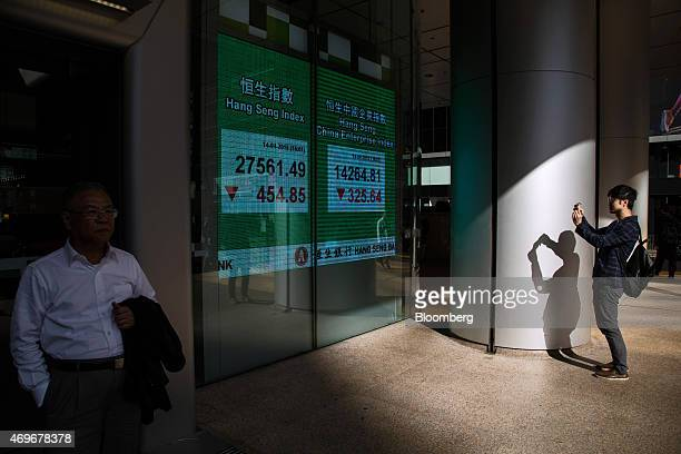 A man takes a photograph of an electronic display showing the closing figure of the Hang Seng Index left and the Hang Seng China Enterprise Index at...