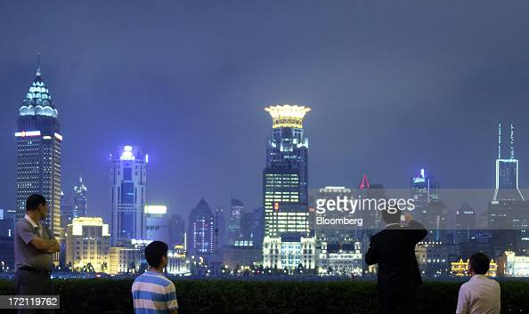 A man takes a photograph of buildings in the Bund area as they stand illuminated at night in Shanghai China on Friday June 28 2013 China's President...