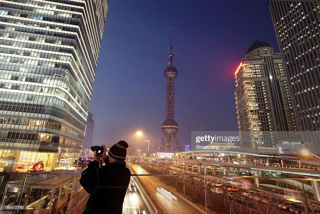A man takes a photograph of commercial buildings at dusk in the Pudong area of Shanghai, China, on Wednesday, Jan. 30, 2013. China's economic growth accelerated for the first time in two years as government efforts to revive demand drove a rebound in industrial output, retail sales and the housing market. Photographer: Tomohiro Ohsumi/Bloomberg via Getty Images
