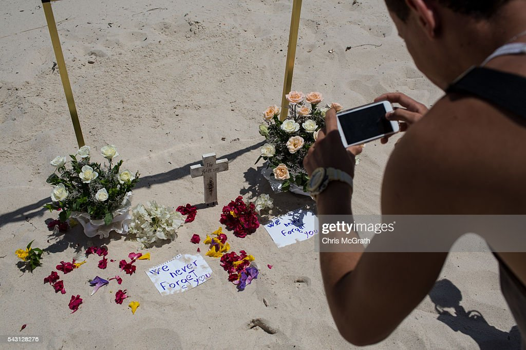 A man takes a photograph of flowers and notes placed at a memorial for the victims of the 2015 Sousse Beach terrorist attack in front of the Imperial Marhaba hotel on June 26, 2016 in Sousse, Tunisia. Today marks the one year anniversary of the Sousse Beach terrorist attack, which killed 38 people including 30 Britons. Before the 2011 revolution, tourism in Tunisia accounted for approximately 7% of the country's GDP. The two 2015 terrorist attacks at the Bardo Museum and Sousse Beach saw tourism numbers plummet even further forcing hotels to close and many tourism and hospitality workers to lose their jobs.