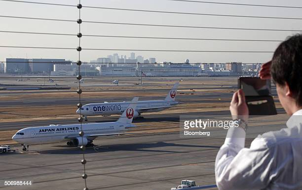 A man takes a photograph of Japan Airlines Corp aircraft taxiing at Haneda Airport in Tokyo Japan on Tuesday Jan 26 2016 JAL is scheduled to report...