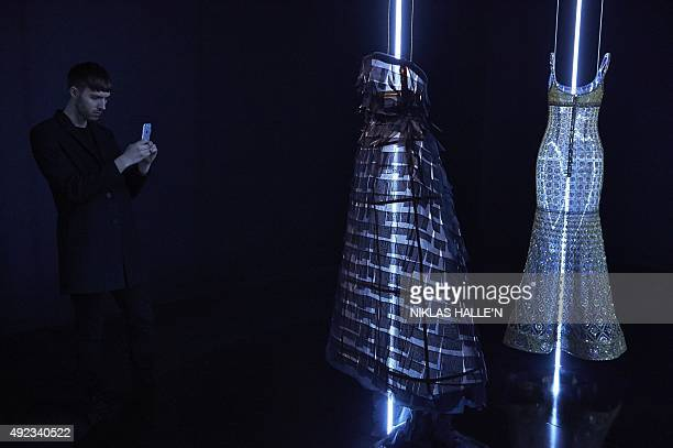 A man takes a photograph of mannequins displaying hautecouture outfits by Fench fashion house Chanel during a pressview of 'Mademoiselle Privé' a...
