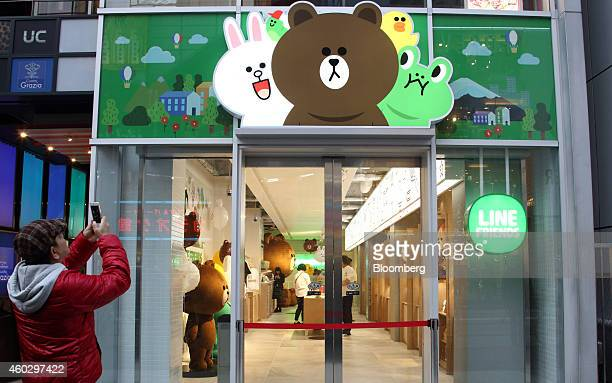 A man takes a photograph of signage outside the Line Friends Store operated by Line Corp in Tokyo Japan on Thursday Dec 10 2014 Line which makes...