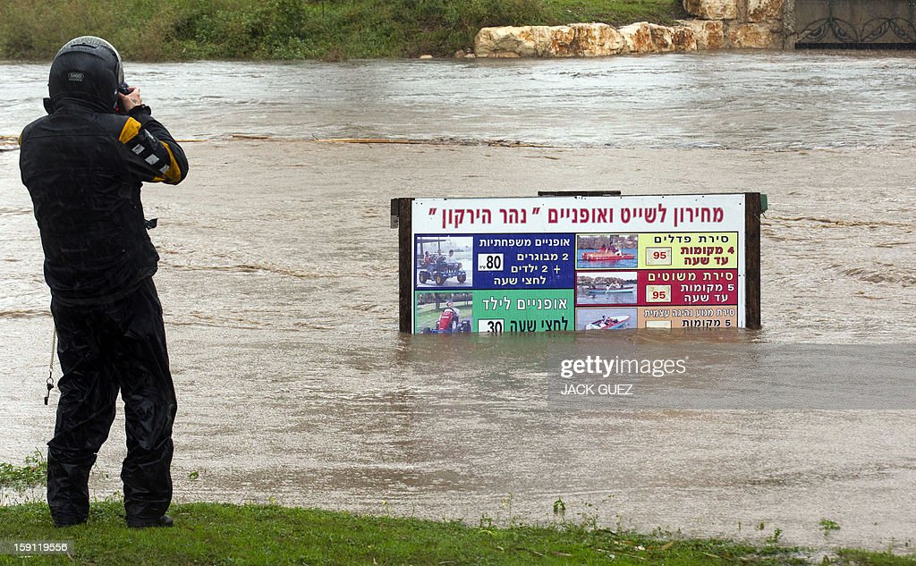 A man takes a photograph of the Ayarkhon River as it flows high following rain storms which also disrupted the road and rail system on January 8, 2013, in the Mediterranean coastal city of Tel Aviv.