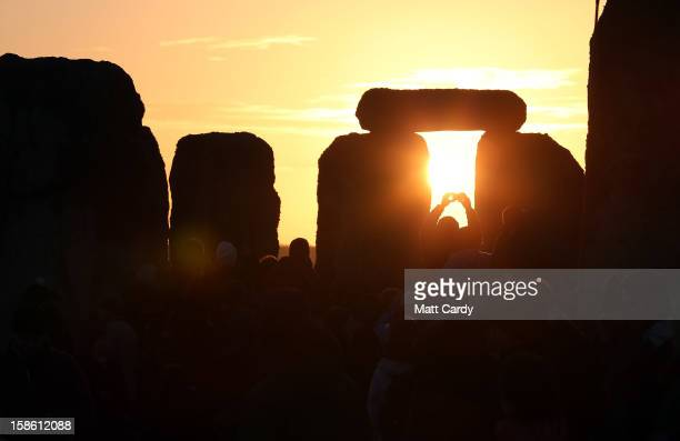 A man takes a photograph of the sunrise as druids pagans and revellers celebrate the winter solstice at Stonehenge on December 21 2012 in Wiltshire...