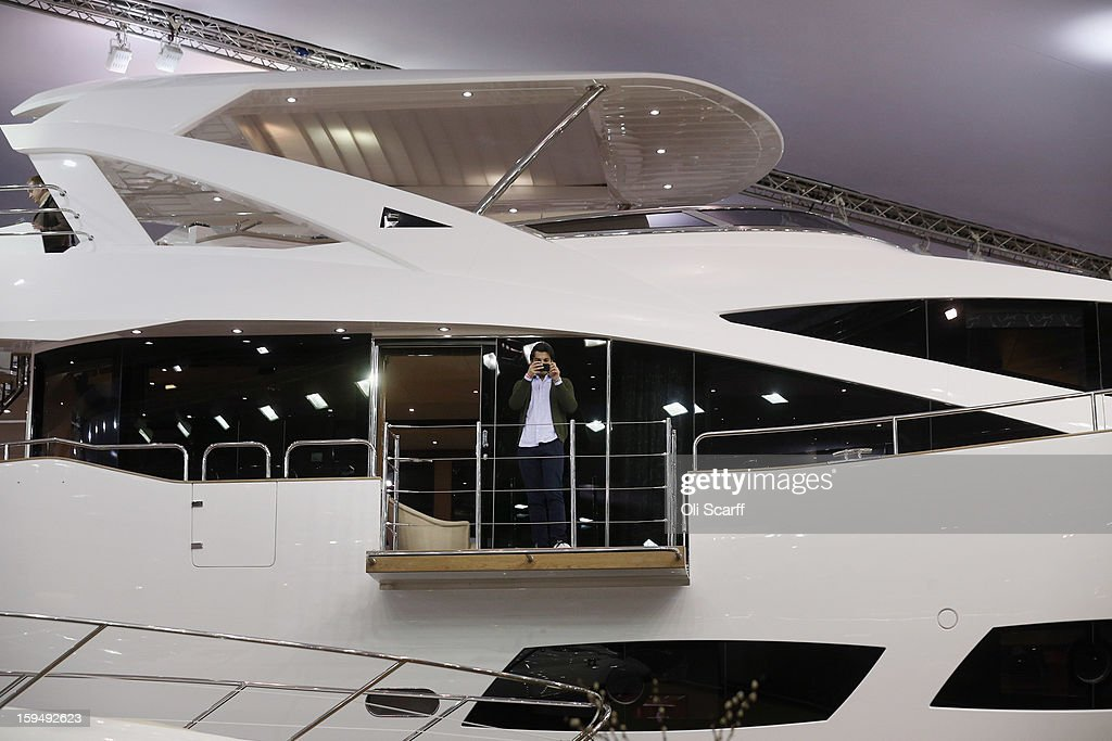 A man takes a photograph on his mobile phone from a balcony of a powerboat on the Sunseeker stand at the 2013 London Boat Show, held at the ExCeL Centre, on January 14, 2013 in London, England. Until January 20, 2013 the London Boat Show will showcase, demonstrate and sell maritime equipment ranging from luxury yachts to dinghies.