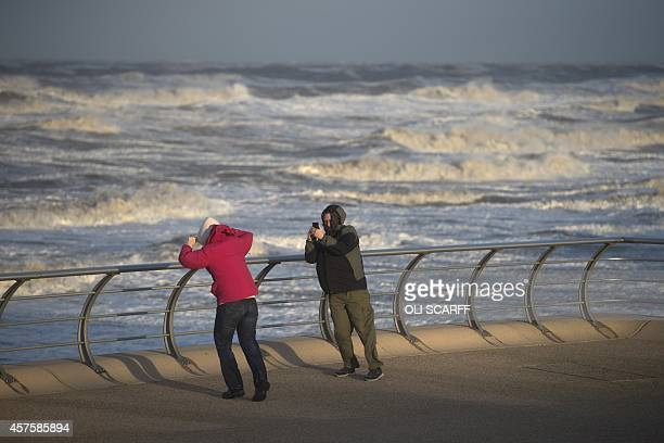 A man takes a photograph on his mobile phone in strong winds on Blackpool seafront brought about by the remnants of Hurricane Gonzalo in Blackpool...