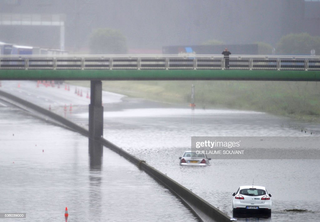 A man takes a photograph on May 31, 2016 in Saran, on a bridge over the A10 highway, flooded due to heavy rainfall. The Loiret department is under red flood alert and France's weather agency Meteo France maintained today 18 departments are under orange alert. / AFP / GUILLAUME