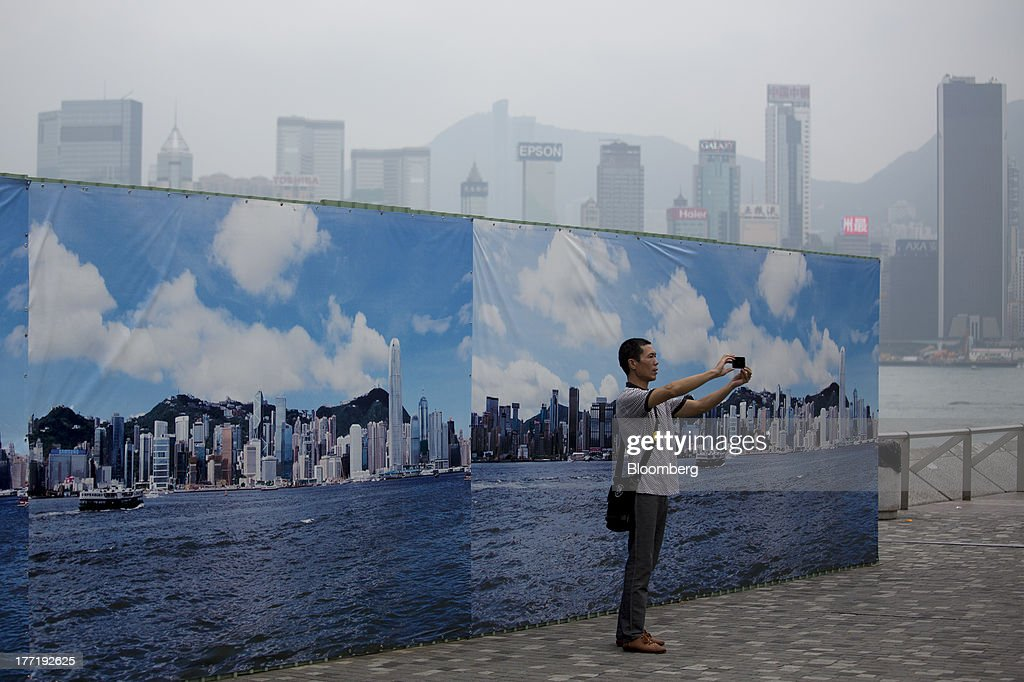 A man takes a photograph standing in front of a structure covered with an image of the Hong Kong island skyline at the waterfront in the Tsim Sha Tsui area of Hong Kong, China, on Thursday, Aug. 22, 2013. Hong Kongs air pollution index reached very high level today as a tropical storm that passed through Taiwan trapped pollutants and blanketed the city in haze, triggering a government health warning. Photographer: Jerome Favre/Bloomberg via Getty Images