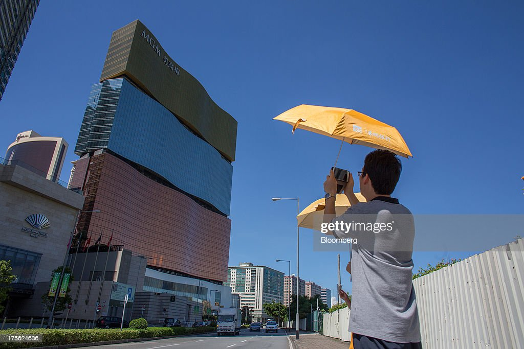 A man takes a photograph while holding an umbrella outside the MGM Macau, operated by MGM China Holdings Ltd., in Macau, China, on Sunday, Aug. 4, 2013. MGM China Holdings is scheduled to release second quarter results on Aug. 6. Photographer: Lam Yik Fei/Bloomberg via Getty Images