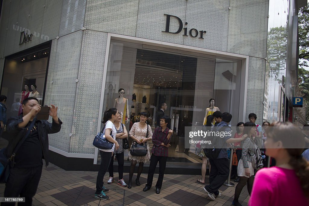 A man takes a photograph while people wait to enter a Christian Dior SA store in the Tsim Sha Tsui area of Hong Kong, China, on Tuesday, April 30, 2013. Financial Secretary John Tsang on Feb. 27 projected annual growth of 1.5 percent to 3.5 percent this year following 2012's 1.4 percent, the weakest rate since 2009 as Europe's sovereign debt crisis sapped global demand. Photographer: Lam Yik Fei/Bloomberg via Getty Images