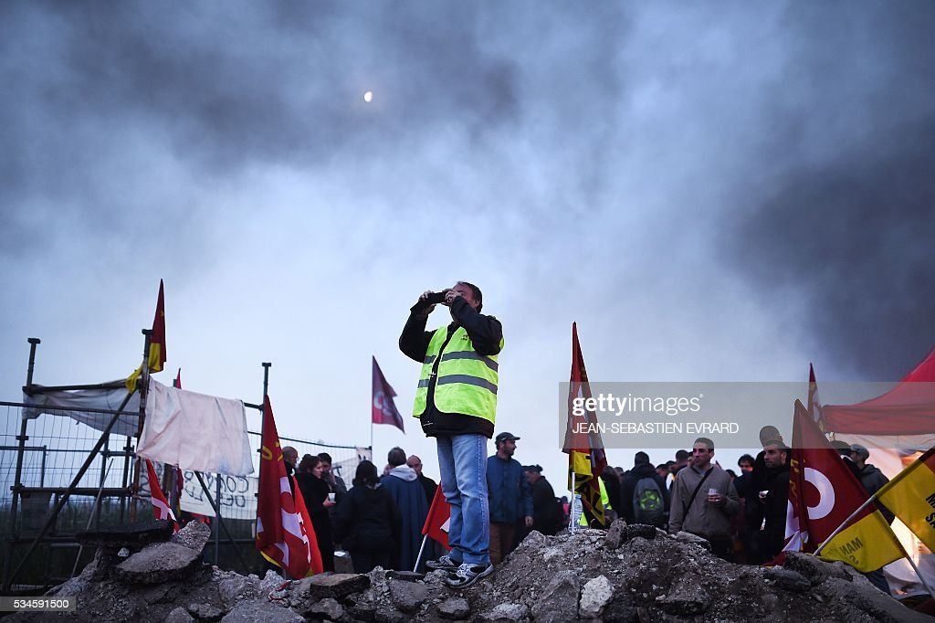 A man takes a photography as workers on strike block the access to an oil depot near the Total refinery of Donges, western france, on May 27, 2016 to protest against the government's planned labour law reforms. The French government's labour market proposals, which are designed to make it easier for companies to hire and fire, have sparked a series of nationwide protests and strikes over the past three months. French unions on May 27 called on workers to 'continue and step up their action', as a wave of strikes against a disputed labour law disrupted transport and fuel supplies. / AFP / JEAN