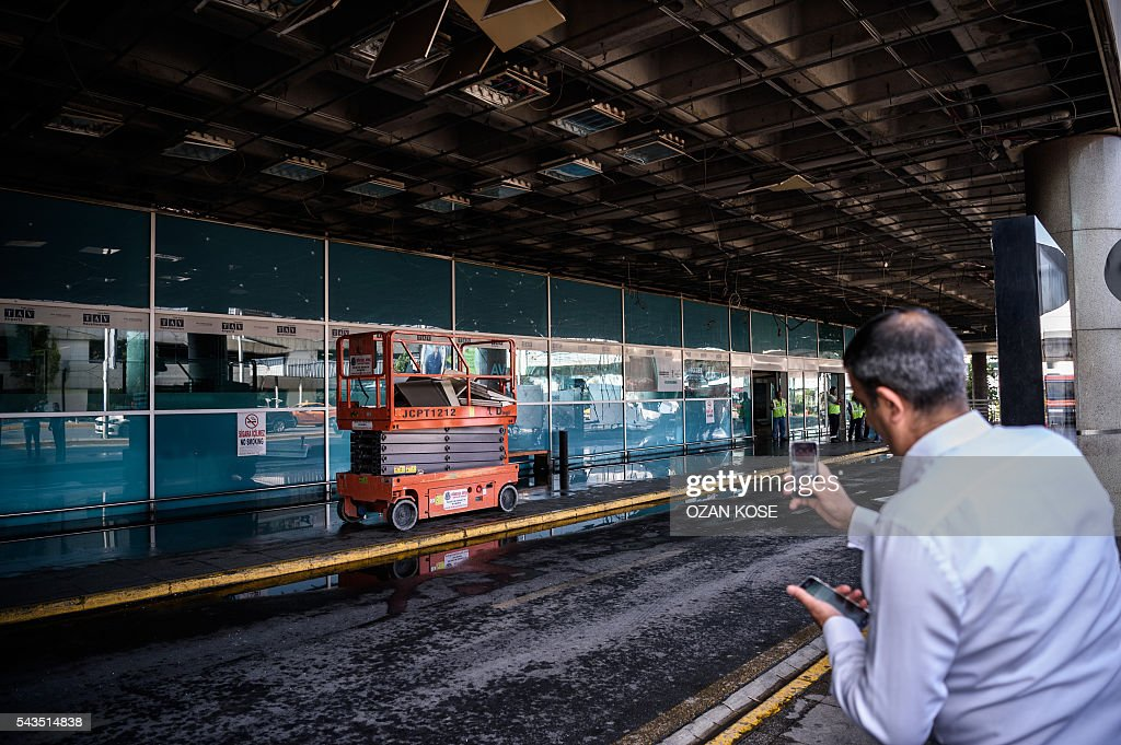 A man takes a picture as metropolitan municipality employees work at the explosions and attacks site outside Ataturk airport's international arrivals terminal on June 29, 2016, a day after a suicide bombing and gun attack targeted Istanbul's airport, killing at least 36 people. A triple suicide bombing and gun attack that occurred on June 28, 2016 at Istanbul's Ataturk airport has killed at least 36 people, including foreigners, with Turkey's prime minister saying early signs pointed to an assault by the Islamic State group. / AFP / OZAN
