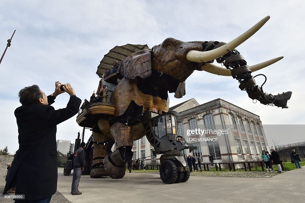 A man takes a picture as people ride a mechanical elephant made of wood and steel at 'Les Machines de L'Ile' ('Machines of the Isle of Nantes') in Nantes, western France, on February 6, 2016. / AFP / LOIC VENANCE