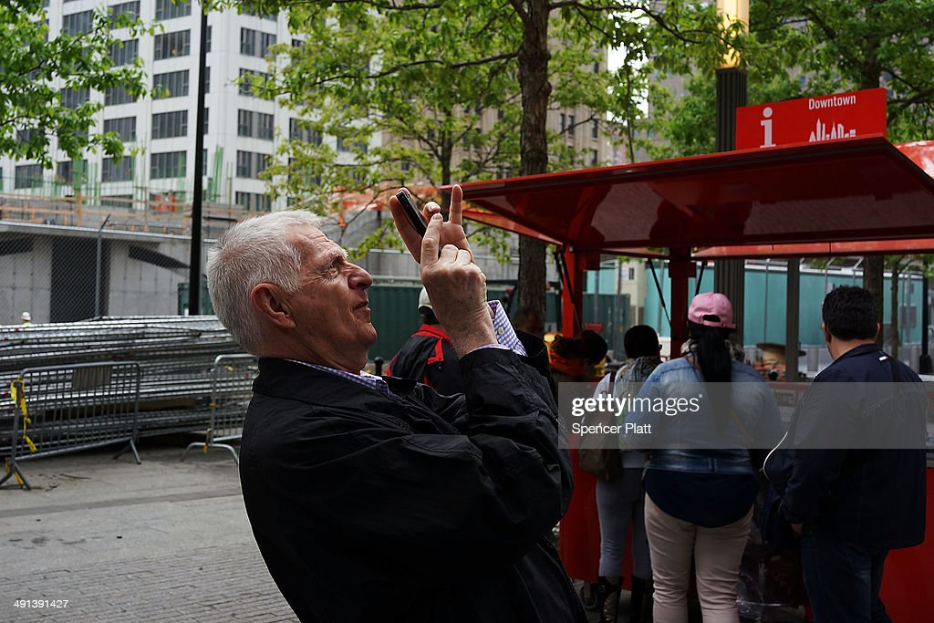 A man takes a picture at the Ground Zero memorial site after authorities opened the plaza to the public free of charge on May 16, 2014 in New York City. Prior to today, visitors had to wait in line to enter a barricaded area which includes the newly dedicated National September 11 Memorial Museum. Together with the museum, Ground Zero has become one of the top tourist attractions in the nation with tens of thousands of visitors expected yearly.
