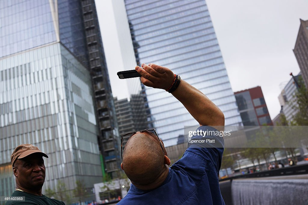 A man takes a picture at the North reflecting pool at the Ground Zero memorial site after authorities opened the plaza to the public free of charge on May 16, 2014 in New York City. Prior to today, visitors had to wait in line to enter a barricaded area which includes the newly dedicated National September 11 Memorial Museum. Together with the museum, Ground Zero has become one of the top tourist attractions in the nation with tens of thousands of visitors expected yearly.