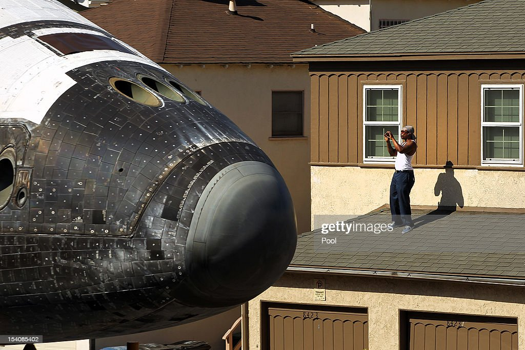 A man takes a picture from a rooftop as the Endeavour Space Shuttle makes its way toward the California Science Center on October 13, 2012 in Inglewood, California. Endeavour is on its last mission - a 12-mile creep through city streets, past an eclectic mix of strip malls, mom-and-pop shops, tidy lawns and faded apartment buildings. Its final destination is the California Science Center in South Los Angeles where it will be put on display. NASA's Space Shuttle Program ended in 2011 after 30 years and 135 missions.