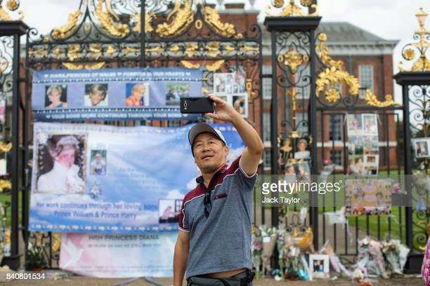 A man takes a picture in front floral tributes photographs and messages sat outside an entrance gate to Kensington Palace ahead of the 20th...