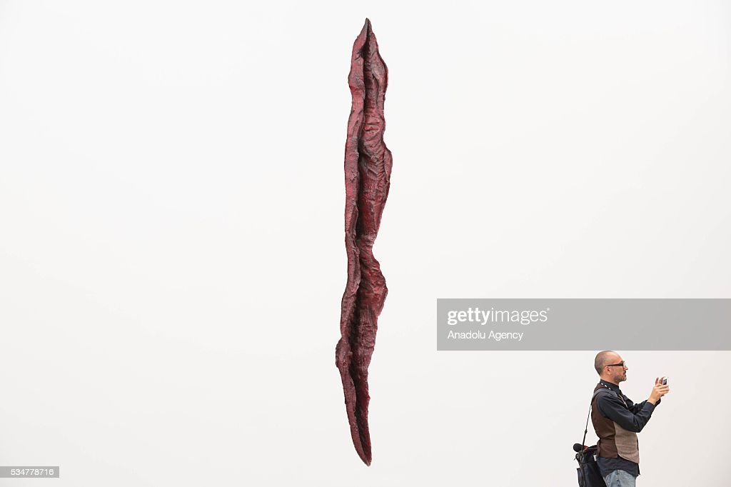 A man takes a picture next to one of the artworks by Indian-British sculptor Anish Kapoor during the exhibition press preview of 'Archaeology: Biology' at University Museum of Contemporary Art in Mexico City, Mexico on May 27, 2016. This exhibition offers a wide-ranging perspective on Kapoors workwith sculptures dating from 1980 to 2016.