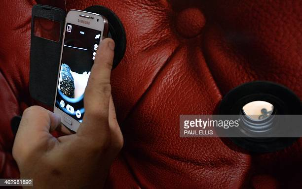 A man takes a picture of a cake model of a women through a peephole in an exhibit depicting the book and film Fifty Shades of Grey during the final...